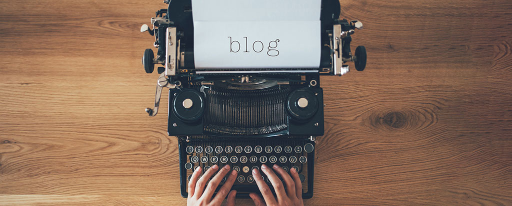 "an image of someone typing on a type writer with the word ""blog"" on the paper to represent the Parasec blog."