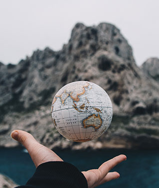 an image of a human hand tossing up a small ball that looks like a planet earth globe