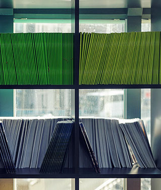 an image of a bookshelf with lots of colorful folders on its shelves