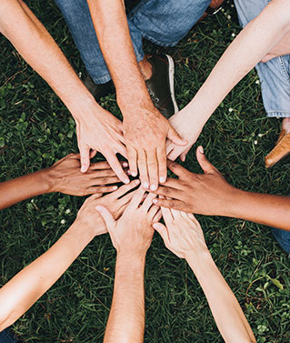 an image of a group of people with their hands in a circle to represent our company culture