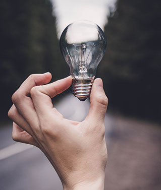 an image of a human hand holding a lightbulb between forefinger and thumb