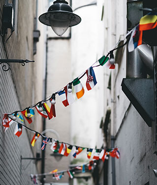 an image of a long string of small country flags strung in a zigzag patter between the walls of a narrow backally