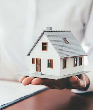 an image of a person holding a model of a house to represent our real property services