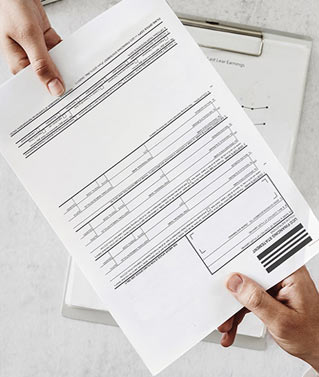 a truncated image of two people passing documents to each other over a desk with clipboard on top of it