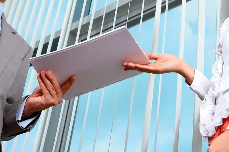 Image of woman handing man paperwork to represent a registered agent delivering SOP